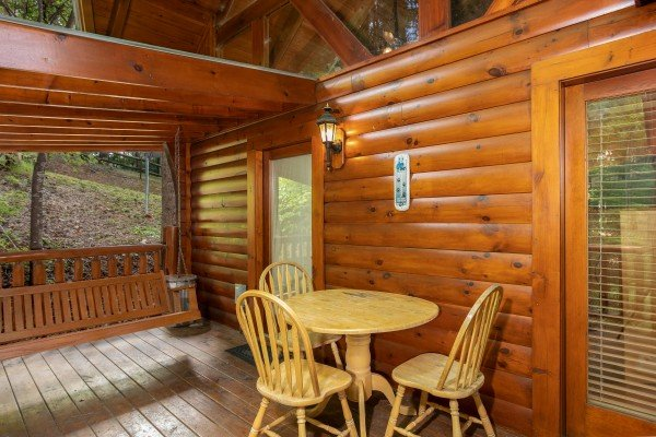 Dining space for three on the deck at Dreams Do Come True, a 1-bedroom cabin rental located in Pigeon Forge