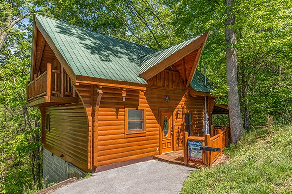 Looking at the cabin and front porch at Dreams Do Come True, a 1-bedroom cabin rental located in Pigeon Forge