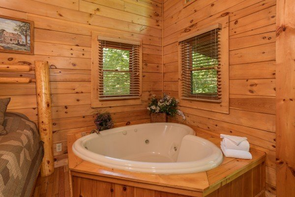 Heart-shaped jacuzzi in a bedroom at Dreams Do Come True, a 1-bedroom cabin rental located in Pigeon Forge