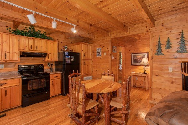 Dining space for four in the kitchen with black appliances at Dreams Do Come True, a 1-bedroom cabin rental located in Pigeon Forge