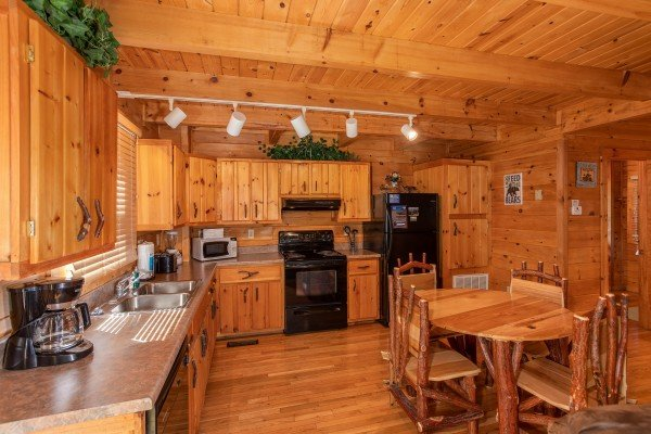Dining table for four in the kitchen with black appliances at Dreams Do Come True, a 1-bedroom cabin rental located in Pigeon Forge