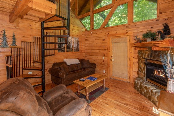 Living room with a fireplace and spiral staircase at Dreams Do Come True, a 1-bedroom cabin rental located in Pigeon Forge