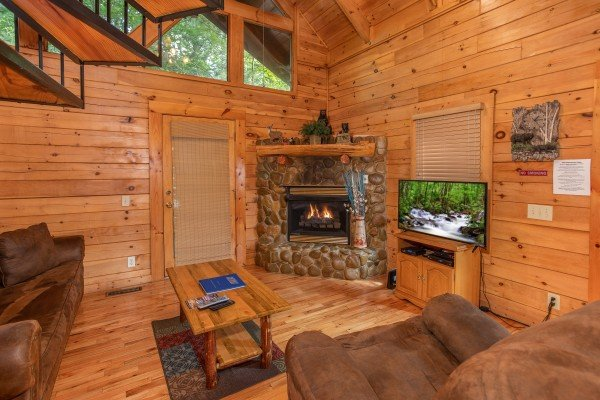 Living room with a fireplace, television, and vaulted ceiling at Dreams Do Come True, a 1-bedroom cabin rental located in Pigeon Forge