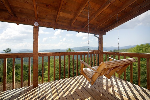 Covered deck with porch swing at Sweet Serenity, a 1 bedroom cabin rental located in Pigeon Forge