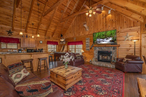 Living room and kitchen with breakfast bar at Bearfoot Adventure, a Gatlinburg Cabin rental