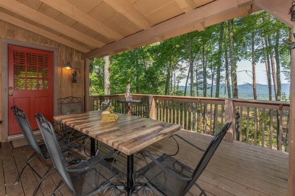 Dining for six on a covered porch at Bearfoot Adventure, a 2 bedroom cabin rental located in Gatlinburg