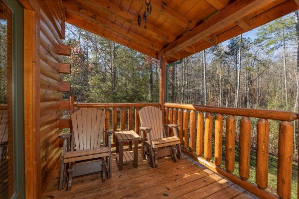 Two adirondack chairs on a covered deck at 3 Crazy Cubs, a 5 bedroom cabin rental located in Pigeon Forge