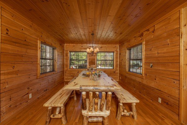 Dining table with long benches and log chairs at 3 Crazy Cubs, a 5 bedroom cabin rental located in Pigeon Forge