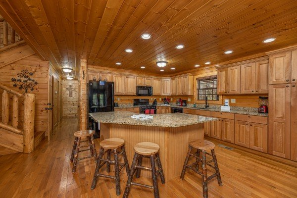 Kitchen island with four stools at 3 Crazy Cubs, a 5 bedroom cabin rental located in Pigeon Forge