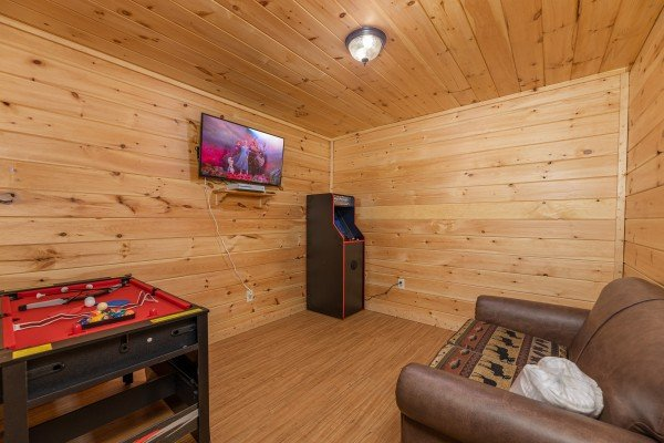 Small pool table, arcade game, and TV in a small game room at 3 Crazy Cubs, a 5 bedroom cabin rental located in Pigeon Forge