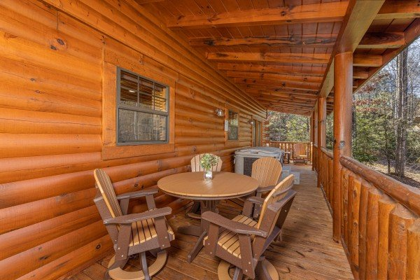 Dining table for four on a covered deck at 3 Crazy Cubs, a 5 bedroom cabin rental located in Pigeon Forge