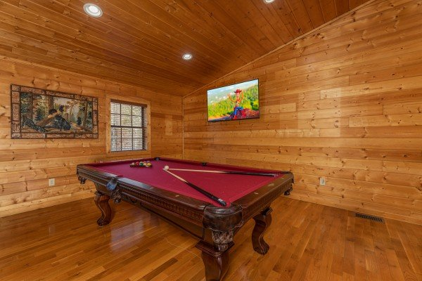 Red felt pool table and TV in a game loft at 3 Crazy Cubs, a 5 bedroom cabin rental located in Pigeon Forge