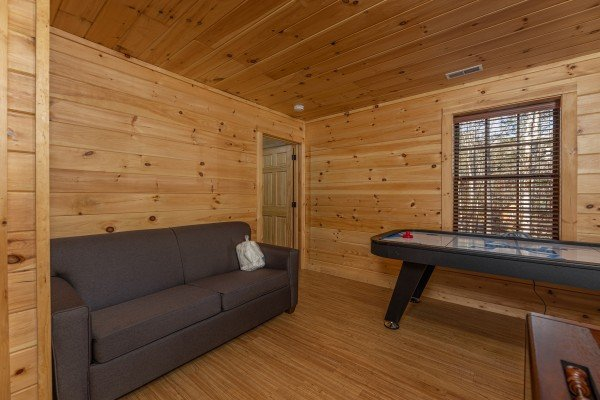 Sofa and shuffleboard in the game room at 3 Crazy Cubs, a 5 bedroom cabin rental located in Pigeon Forge