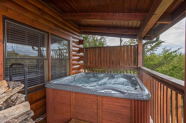 Hot tub on a covered deck with a privacy fence at Eagle's Nest, a 2-bedroom cabin rental located in Sevierville