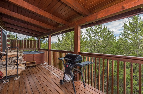 Propane grill, firewood, and a hot tub on a covered deck at Eagle's Nest, a 2-bedroom cabin rental located in Sevierville