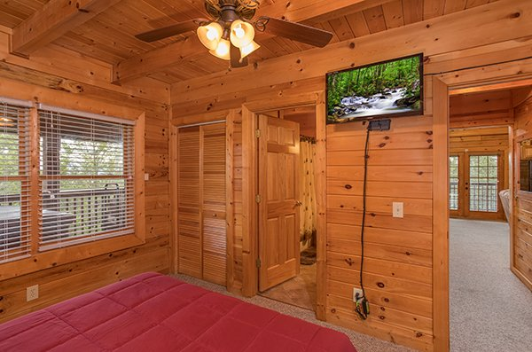 Wall-mounted television in the bedroom at at Eagle's Nest, a 2-bedroom cabin rental located in Sevierville
