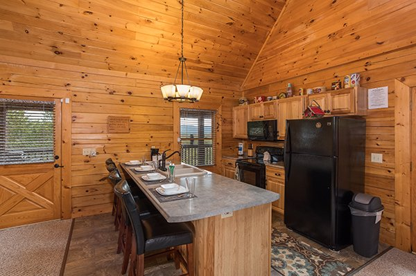 Kitchen with black appliances and counter seating for four at Eagle's Nest, a 2-bedroom cabin rental located in Sevierville