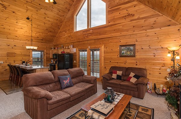 Living room with a sofa and loveseat adjacent to a dining space at Eagle's Nest, a 2-bedroom cabin rental located in Sevierville
