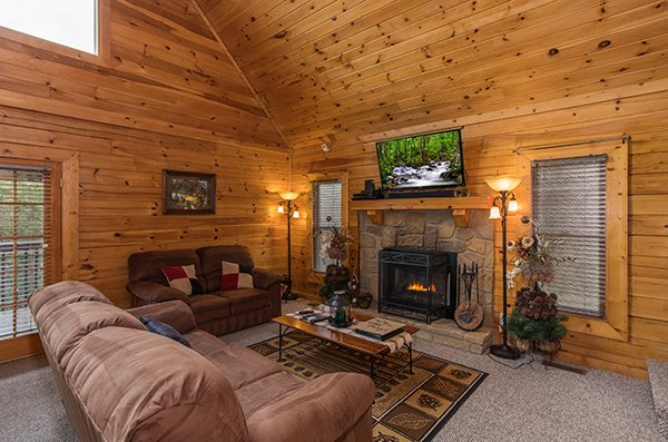 Living room with stone fireplace and tv at Eagle's Nest, a 2-bedroom cabin rental located in Sevierville