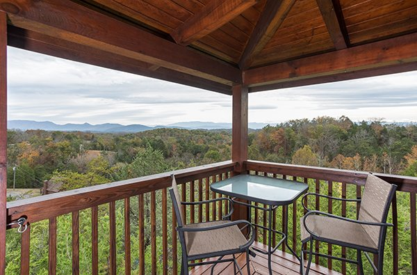 Bistro set on the covered deck at Eagle's Nest, a 2-bedroom cabin rental located in Sevierville