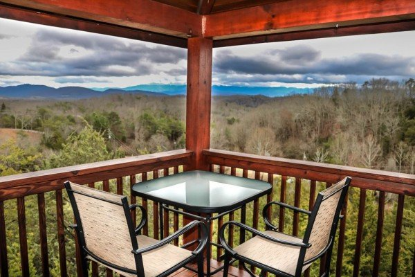 Outdoor dining space for two overlooking the mountains from the covered deck at Eagle's Nest, a 2-bedroom cabin rental located in Sevierville