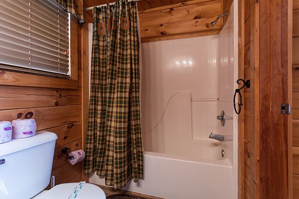 Bathroom with a tub and shower at 5 Star Celebration, a 1 bedroom cabin rental located in Pigeon Forge