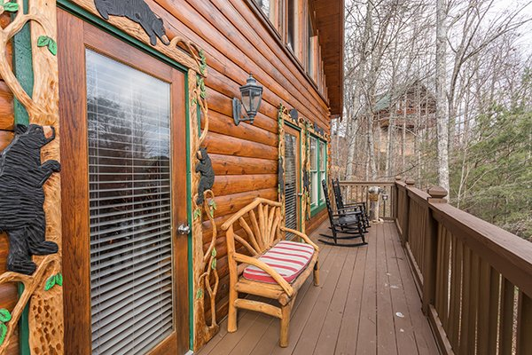 Deck with bench and rocking chairs at 5 Star Celebration, a 1 bedroom cabin rental located in Pigeon Forge