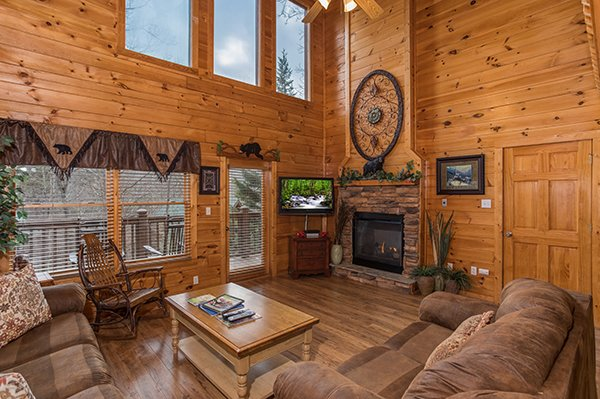 Great room with fireplace and television at 5 Star Celebration, a 1 bedroom cabin rental located in Pigeon Forge