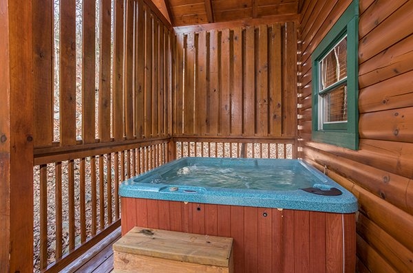 Outdoor hot tub with privacy fence at 5 Star Celebration, a 1 bedroom cabin rental located in Pigeon Forge