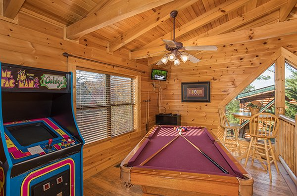 Arcade game and pool table in the loft at 5 Little Cubs, a 2 bedroom cabin rental located in Pigeon Forge