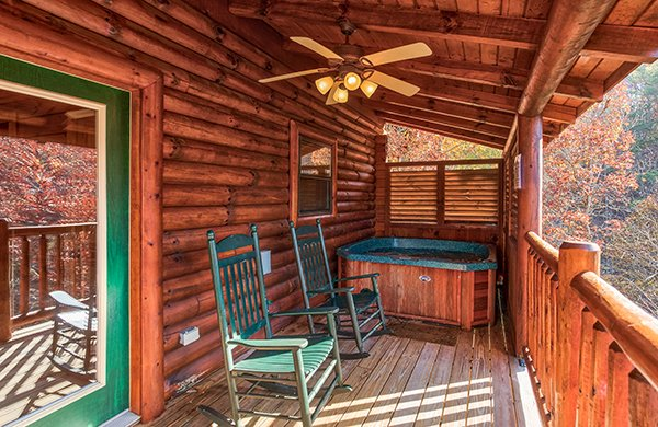 Hot tub and rocking chairs on a covered porch at 5 Little Cubs, a 2 bedroom cabin rental located in Pigeon Forge