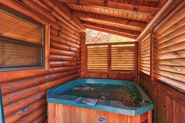 Hot tub with privacy fence on a covered porch at 5 Little Cubs, a 2 bedroom cabin rental located in Pigeon Forge