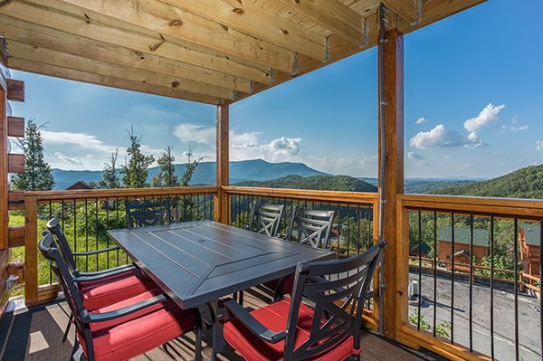 Dining table for five on a covered deck at The Sugar Shack, a 2 bedroom cabin rental located in Pigeon Forge