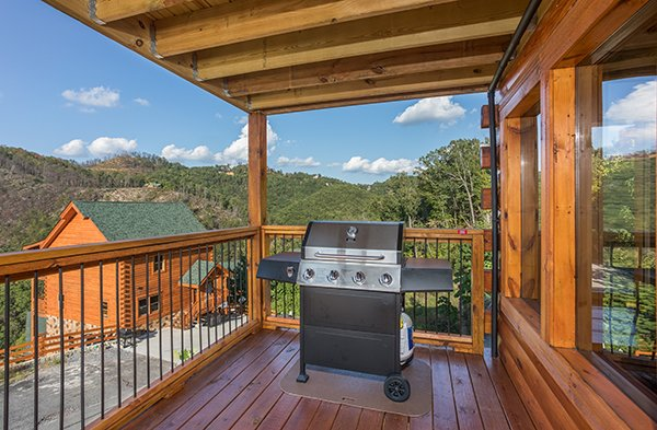 Propane grill on a covered deck at The Sugar Shack, a 2 bedroom cabin rental located in Pigeon Forge