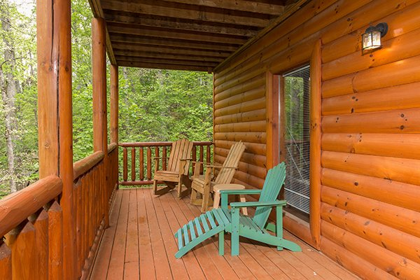 Adirondack chairs and lounge chair on a covered deck at Tennessee Treasure, a 3 bedroom rental cabin in Pigeon Forge