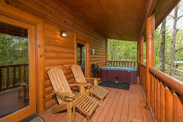 Lounge chairs and hot tub on a covered deck at Tennessee Treasure, a 3 bedroom cabin rental located in Pigeon Forge