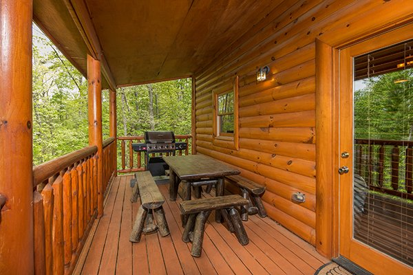 Dining table and grill on a covered deck at Tennessee Treasure, a 3 bedroom cabin rental located in Pigeon Forge