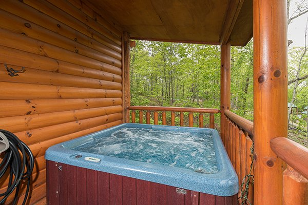 Hot tub on a covered deck at Tennessee Treasure, a 3 bedroom cabin rental located in Pigeon Forge
