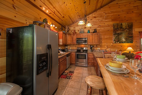 Kitchen with stainless appliances and dining table at Tennessee Treasure, a 3 bedroom cabin rental located in Pigeon Forge