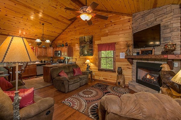 Living room and kitchen on the main floor at Tennessee Treasure, a 3 bedroom cabin rental located in Pigeon Forge