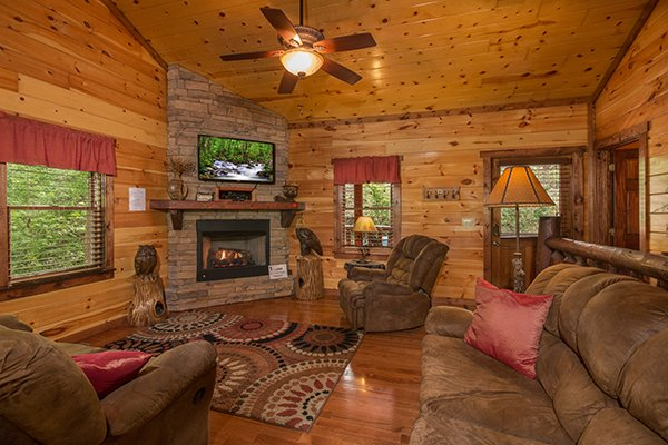 Living room with fireplace and TV at Tennessee Treasure, a 3 bedroom cabin rental located in Pigeon Forge