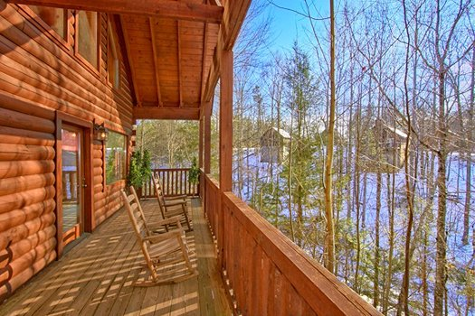 Rocking chairs on a covered porch overlooking winter views at Secluded Pleasure, a 1 bedroom cabin rental located in Pigeon Forge