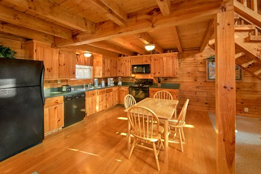 Dining room for four and kitchen with black appliances at Secluded Pleasure, a 1 bedroom cabin rental located in Pigeon Forge
