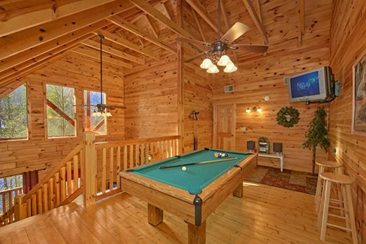 Pool table and TV in the game loft at Secluded Pleasure, a 1 bedroom cabin rental located in Pigeon Forge