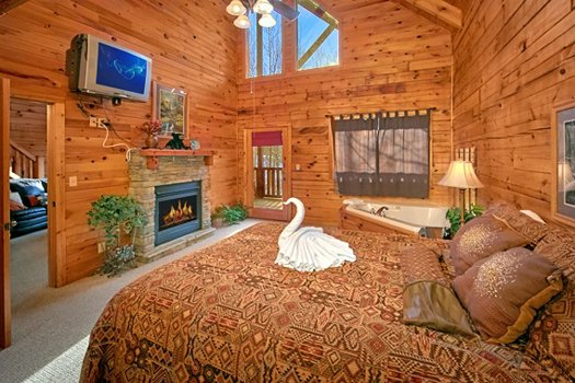 King bedroom with a TV, fireplace, and jacuzzi at Secluded Pleasure, a 1 bedroom cabin rental located in Pigeon Forge