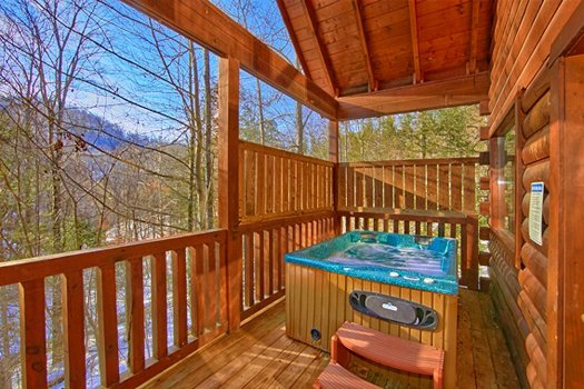 Hot tub on a covered deck with privacy fence at Secluded Pleasure, a 1 bedroom cabin rental located in Pigeon Forge