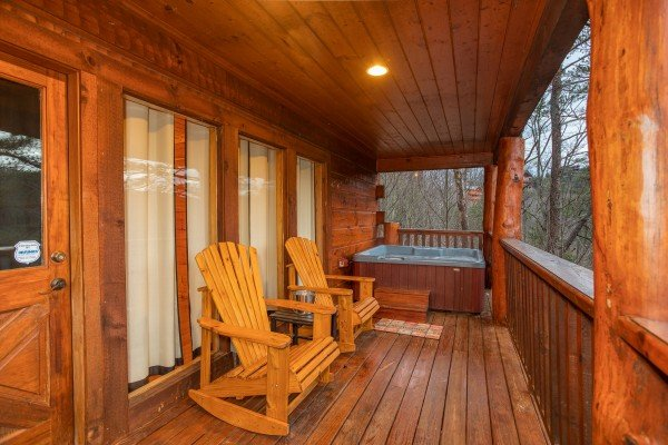 Two Adirondack rockers and a hot tub on the covered deck at Black Bear Hide-out, a 3-bedroom cabin rental located in Pigeon Forge