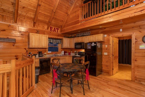 Dining space for four and the kitchen with black appliances at Black Bear Hide-out, a 3-bedroom cabin rental located in Pigeon Forge