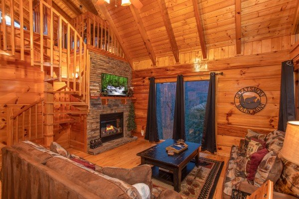Living room with a wooden spiral staircase, TV, fireplace, and deck access at Black Bear Hide-out, a 3-bedroom cabin rental located in Pigeon Forge