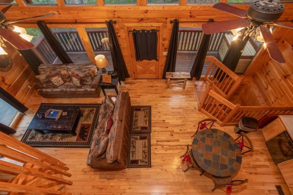 Looking down at the living and dining space from the upper floor at Black Bear Hide-out, a 3-bedroom cabin rental located in Pigeon Forge
